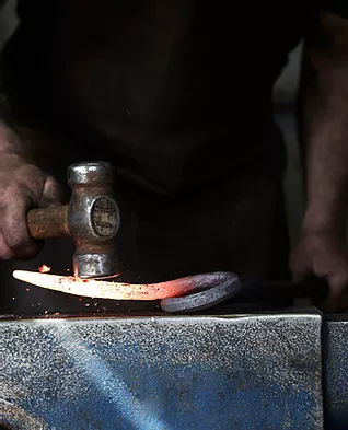 A blacksmith hammering a molten metal on an anvil